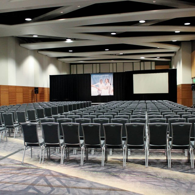 Large room with rows of chairs facing a stage and screen