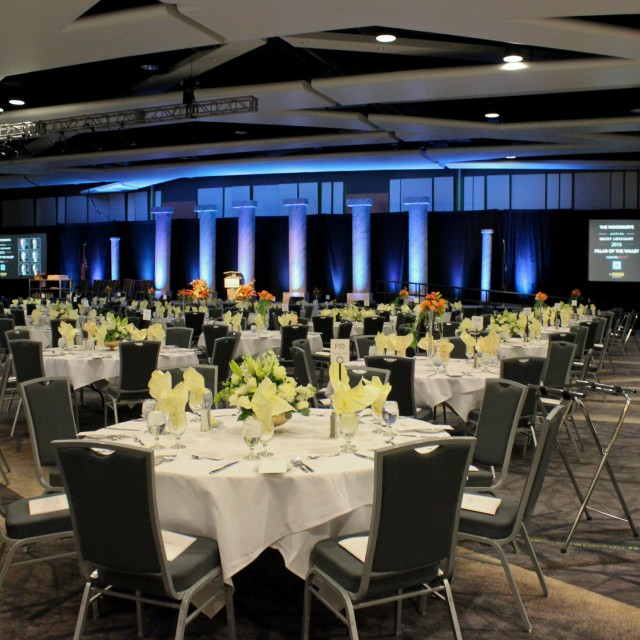 Large ballroom with round tables set for a formal dinner