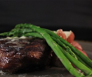 Steak topped with asparagus with potatoes